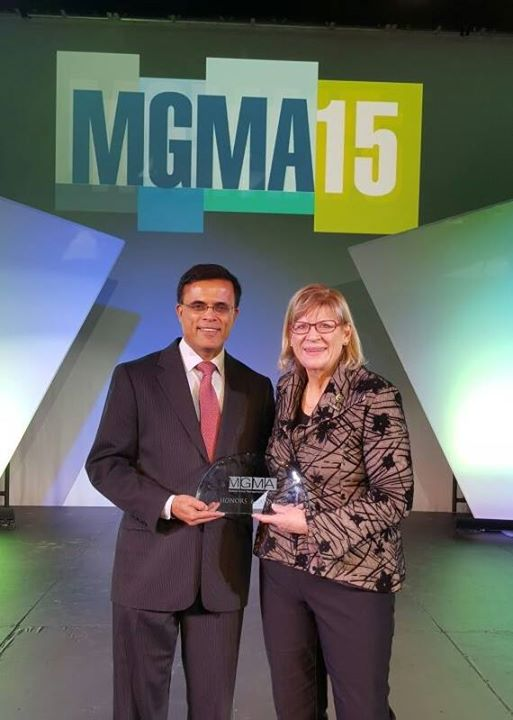 Dr. Sumir Sahgal (left) receiving his 'Physician Executive of the Year Award' from MGMA Board Chair, Deborah J. Wiggs (right)